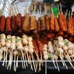 Kott i mangder fran ett typiskt matstalle i Bangkok